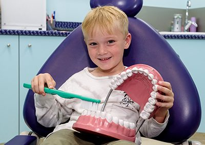 young boy in dentist chair brushing fake teeth at a dental clinic for kids sunshine coast