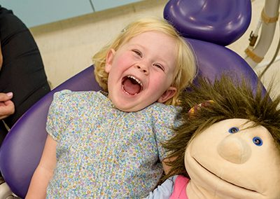 blonde haired girl toddler at dentist laughing in purple dental chair