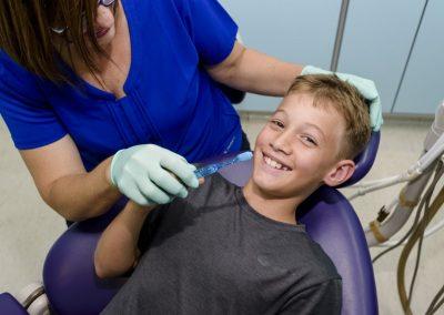 kids dentist sunshine coast brushing boys teeth in dental exam chair